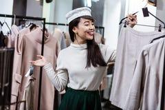 Brunette asian beautiful woman in a nice headwear choosing a skirt royalty free stock image