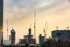 New skyscrapers under construction. With tall cranes against glowing sky. Construction business and industry, urbanisation, urban sprawl real estate bubble Stock Photography