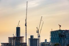 New skyscrapers under construction. Silhouette of new skyscrapers under construction with tall cranes against colourful sky. Construction business and industry Royalty Free Stock Photography
