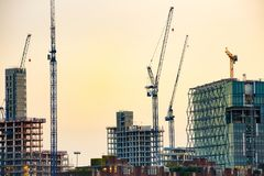 New skyscrapers under construction. With tall cranes against colourful sky. Construction business and industry, urbanisation, urban sprawl real estate bubble Royalty Free Stock Photos