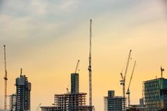 New skyscrapers under construction. With tall cranes against yellow sky. Construction business and industry, urbanisation, urban sprawl real estate bubble Royalty Free Stock Image