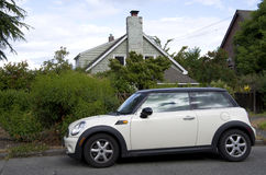 New small car old house. A modern small car in front of an old house stock photo