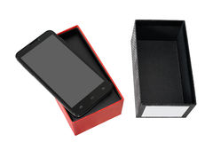 New smart phone in the box. Modern new mobile phone in the box, isolated on a white background Royalty Free Stock Photography
