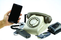 New smart phone with old telephone on white background. New communication technology.  Royalty Free Stock Images