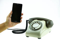 New smart phone with old telephone on white background. New communication technology.  Stock Photography