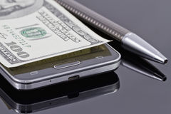 New smartphone, ballpoint pen and hundred dollars Royalty Free Stock Photos