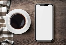 New smartphone similar to iphone X top view on old wood table with cloth and coffee. New smartphone similar to iphone X top view on white wood desk with coffee royalty free stock photos