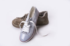 New sneaker is leaning on  old wear out one. Royalty Free Stock Photo