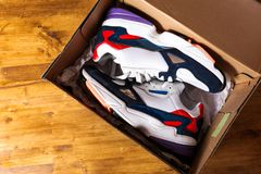 New sneakers in the box on wooden background stock images