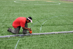 New Soccer field. A worker finishing a new artificial grass soccer field Stock Image