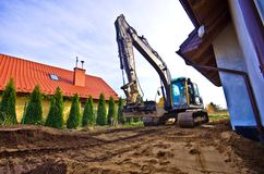 New soil for home garden. An excavator working near a new private house, levelling the new soil brought in for the garden Stock Photography