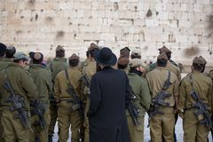 New soldiers for protecting pr. Jew man is watching over soldiers close to Western Wall in Jerusalem Royalty Free Stock Photography