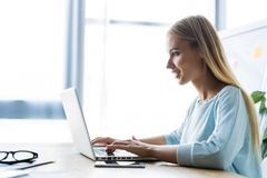 New solution every day. Confident young woman in smart casual wear working on laptop while sitting at her working place royalty free stock images