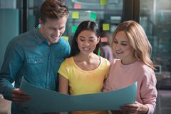 Cheerful colleagues are laboring together with pleasure. New start-up. Joyful men and women are standing in office and holding paper sheet while looking at it Stock Photography