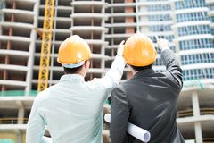 New storey. Rear-view of two foremen pointing at the newly-built storey royalty free stock photo