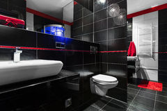New style bathroom idea. Spacious black bathroom with red details, white basin and toilet royalty free stock photography