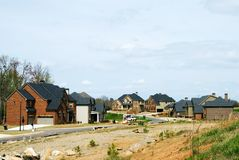 New subdivision build-out. Houses being built in a new area, raw land in the foreground and new construction in the distance Royalty Free Stock Image