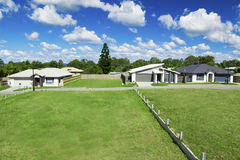 New suburban houses. Sunny, green Australian housing development land with three newly built houses Royalty Free Stock Photography