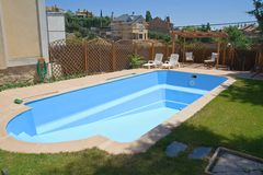 New swimming pool in a garden. Brand new garden swimming pool, empty Royalty Free Stock Photo