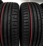 New symmetrical tires on the showcase of car parts store. New all weather tires shows on the showcase of tire shop Royalty Free Stock Photos