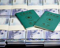 New Taiwan Dollars in stacks with ROC passport Stock Photos
