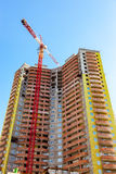 New tall apartment building under construction with crane agains Royalty Free Stock Photo