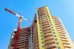 New tall apartment building under construction with crane Stock Photos