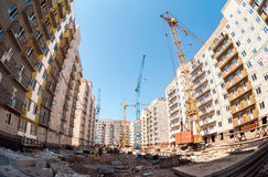 New tall apartment buildings under construction with cranes. Against blue sky background Stock Photography