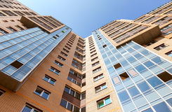 New tall modern apartment building against blue sky. Background Royalty Free Stock Image