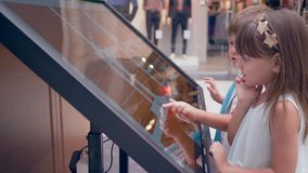 New technologies in self-service, child boy with girlfriend uses touch kiosks For search information about location of. Store at modern shopping mall stock video