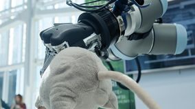 New technologies among us. The hand of the robot takes a soft toy in the shape of a mouse by the tail. Future today.