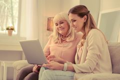 Pleasant young woman showing a laptop to her mother. New technology. Pleasant young women sitting together with her mother while showing her a laptop royalty free stock photos