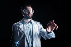 Smart nice man working in the science lab. New technology. Smart nice handsome man wearing safety glasses and looking at the sensory screen while working in the Stock Image