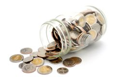 New Thai Baht coins spilling from a glass jar. stock image