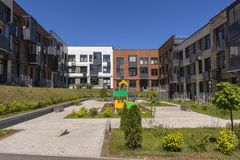 New three-storey residential building. Playground in the yard. New residential area royalty free stock photo
