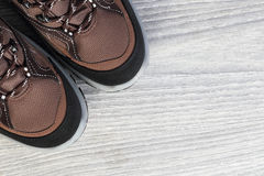 New trekking shoes on wooden background. From above. New brown shoes over white wood backdrop closeup. Footwear background with copy-space on wooden backdrop Royalty Free Stock Images