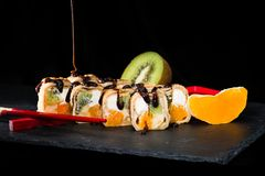 New trend in the Japanese cuisiune. Sweet sushi rolls in pancake royalty free stock image
