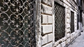 Window with a decorative metal grid of old Venetian times on the wall of an old building, architectural detail royalty free stock photos
