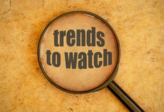 New trends. Magnifying glass over trends to watch text Royalty Free Stock Photo
