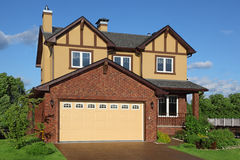 New two-storied brown cottage with built-in garage Stock Images