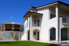 New two-story house with garden. New finished white two-story house with garden, balcony and stairs to the right and unfinished building to the left Royalty Free Stock Images