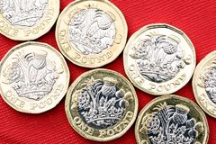 New UK One Pound Coin Currency. New shiny UK Pound Coin currency of silver and gold on a red background. Coins are designed to stop forgery of the English money Stock Photos