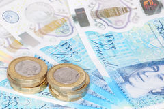 The new UK polymer five pound note and the new 12 sided £1 coin Stock Photography
