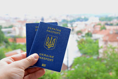New ukrainian blue biometric passport with identification chip on against town background. Royalty Free Stock Image
