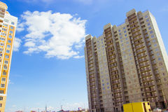 New uncompleted residential high-rise building of reinforced concrete slabs on the background of the blue sky. Social programs and. Affordable housing for young Stock Photo