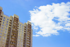 New uncompleted residential high-rise building of reinforced concrete slabs on the background of the blue sky. Social programs and Royalty Free Stock Photos