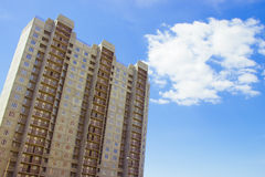 New uncompleted residential high-rise building of reinforced concrete slabs on the background of the blue sky. Social programs and Royalty Free Stock Image