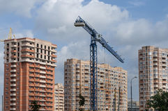 New urban development. Blue construction crane and three new high-rise homes Stock Image