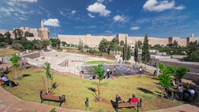 New urban Teddy Park and Tower of David on background under blue sky timelapse hyperlapse in Jerusalem, Israel. Blue cloudy sky and people sitting on bench stock video