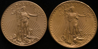 New US Gold Eagle Coin vs. Old US Gold Double Eagle Coin. On black background royalty free stock image